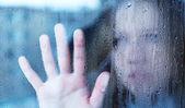 Melancholie a smutné mladá žena u okna v dešti