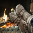 Постер, плакат: Feet in wool socks warming at the fireplace