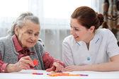 Infermiera cura anziano giocando puzzle con donna senior in casa di cura