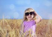 Adorabile bambina bionda con i capelli legati in trecce in posa in enormi occhiali da sole alla moda in un campo di grano dorato ridendo e agitando