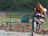 žena na lavičce při používání mobilního telefonu