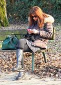žena čekala na lavičce při používání mobilního telefonu