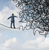 Concetto di rischio confusione business con un uomo daffari su una corda tesa high wire camminando verso un pasticcio aggrovigliato come metafora e simbolo di superare le avversità in strategia e trovare soluzioni attraverso qualificati leadership affrontare ostacoli difficili