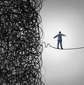 Concetto di business gestione crisi come un funambolo, a pochi passi da un caos aggrovigliato confuso di fili rottura libera di un chiaro percorso di opportunità di rischio come metafora per la gestione delle sfide organizzative per la libertà finanziaria e il successo