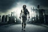 Survivor post apocalittico in maschera antigas, città distrutta in background
