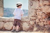 Aranyos kisfiú kint a város hátulnézete