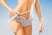 Woman measuring perfect shape of beautiful hips.