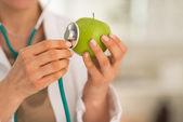 Lékař zkoumá jablko
