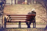 Osamělý muž na lavičce podzim