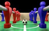 Un biliardino al livello del suolo con un pallone da calcio essendo gareggiato per da un team di blu e rosso pronto a dare il via a una partita di calcio