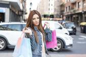Atraktivní dívka drží nákupní tašky na ulici