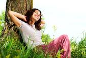 Schöne junge Frau, die im Freien entspannen. Natur