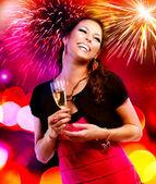 Schönes Mädchen mit Urlaub Make-up hält Glas Champagner