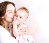 Matka a dítě, líbání a objímání. šťastná rodina