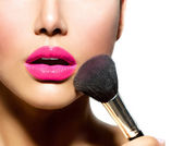 Closeup vyrovnávací make-up. Kosmetická prášku kartáčem pro tvoří