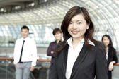 Business woman with colleagues in the background