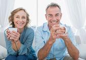 Usmívající se středním věku pár sedící na gauči s kávou