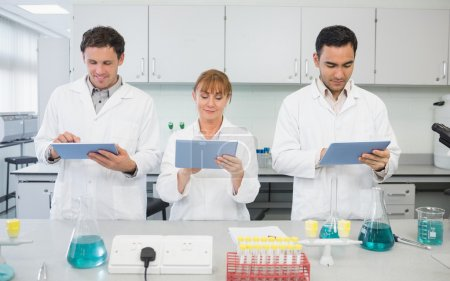 Постер, плакат: Scientists using tablet PCs in the lab, холст на подрамнике