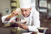 Konzentrierte männliche Pastry Chef Dekoration Dessert in Küche