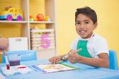 Malý chlapec, malování v učebně u stolu