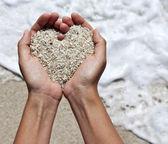 Mildes Herz Gestaltung Frauenhänden oberhalb des Strandes