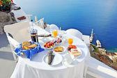 Breakfast on a terrace overlooking the sea in Oia