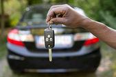 Muž drží klíče od auta