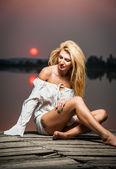 Gyönyörű lány, egy fehér inget, a mólón, a naplemente. Szexi nő hosszú lábakkal ült a mólón. Színes kép egy szépség lány ül a mólón, egy tóra néző