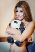 Young blond sensual woman smiling and hugging a panda bear toy. Beautiful young girl without clothes relaxing in her room with a teddy bear. Attractive blonde in cosy scenery
