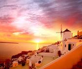 Windmill against colorful sunset, Santorini, Greece
