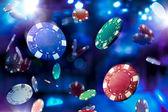 Casinò poker chip cadendo con illuminazione drammatica