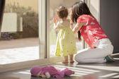 Fiatal Anya gyermekével az ablakból kinézve