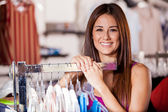Portrait of happy woman looking at camera in clothing store