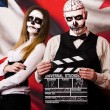 Постер, плакат: Woman and man in mask skull face with movie board slapstick
