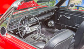 Interior of a 1960s red Ford Mustang