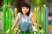 Little asian girl sitting on slide at playground