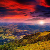 Light beam falls on hillside with autumn forest in mountain on