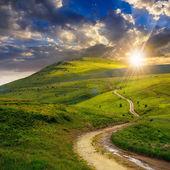 Krajobraz lato. górska ścieżka przez pole zamienia pod górę w niebo na zachodzie słońca