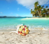 Wedding bouquet of roses on the shore of a tropical beach in the