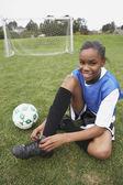 Mladá dívka vázání její fotbal kopačky