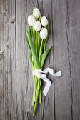 Bouquet of white tulips on wooden table