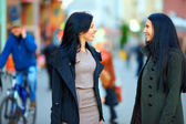 Two happy women talking on crowded city street