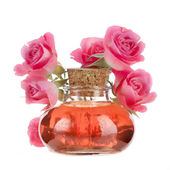 Rose oil in bottle with flowers