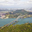Постер, плакат: Aerial view of the Bridge of the Americas at the Pacific entrance to the Panama Canal with Panama City in the background