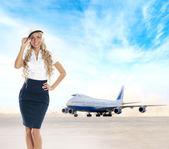 Sexy Stewardess über Hintergrund des Flughafen und Flugzeug