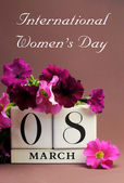 White block calendar for International Women's Day, March 8, decorated with pink and purple flowers (vertical)