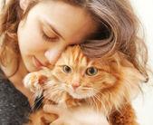 Bellissima giovane donna di 20 anni con un soffice gatto rosso