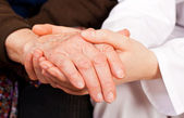 Young doctor holds the elderly woman hands