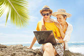 Couple with laptop on the beach, bali