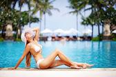 Young beautiful woman sitting near swimming pool